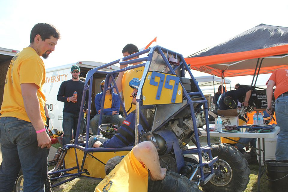 The WVU team works on Car Number 99 in the pits during the 2018 Baja SAE Competition