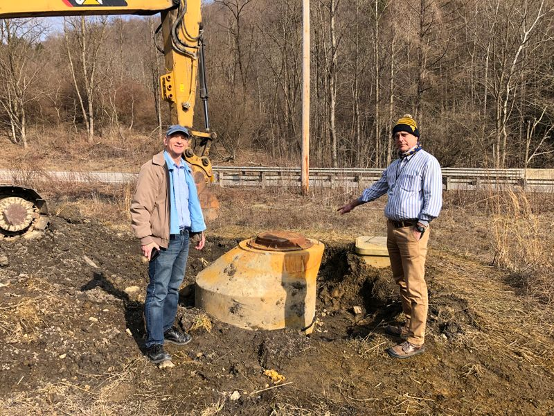 WVU researchers Jeff Skousen and Paul Ziemkiewicz visit the site where an uncontrolled discharge of acidic water flowed through a broken manhole near an acid mine drainage treatment site in Albright, Preston County.