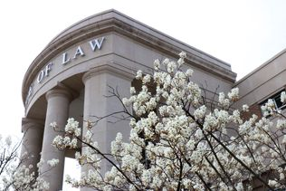 Front of the Law School Building with blooming flowers