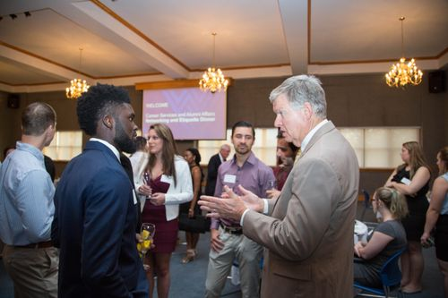 Students and alumni chat at a networking event.