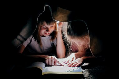 Two young girls read a book via a flashlight while under a blanket