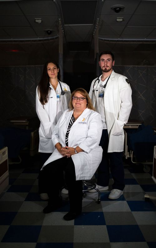 Dr. Crystal Shreeves and Nursing students Caelea Teel and Matt Lechalk stand in a darkened hospital room