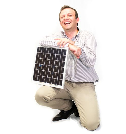 Dr. Kenan Hatipoglu laughs as he holds a solar panel