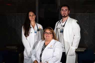 Dr. Sheaves and 2 nursing students in a darkened hospital room