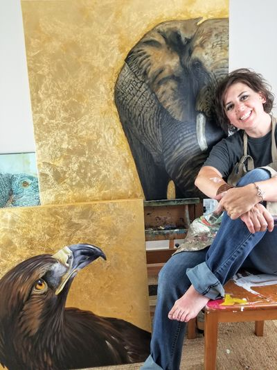 Artists Hilary Clement sits in her studio, barefoot and wearing he painter's apron, in front of original paintings of an elephant and an eagle.