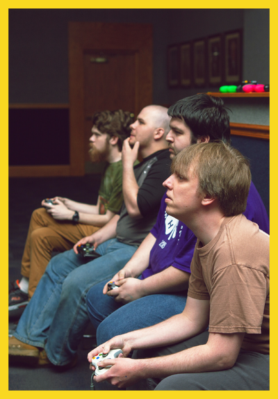 Gamers, mashing their controllers, intently watch the action off-screen.