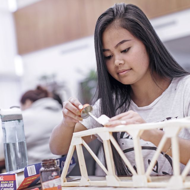 A student experiments with elements of engineering and science to construct a scale-model bridge in the Mary F. Shipper Library.