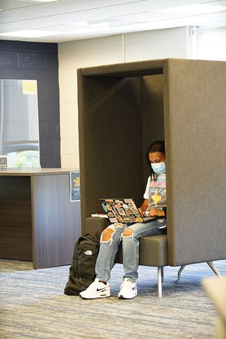A student utilizes one of the library's new study pods that just happens to also promote physical distancing