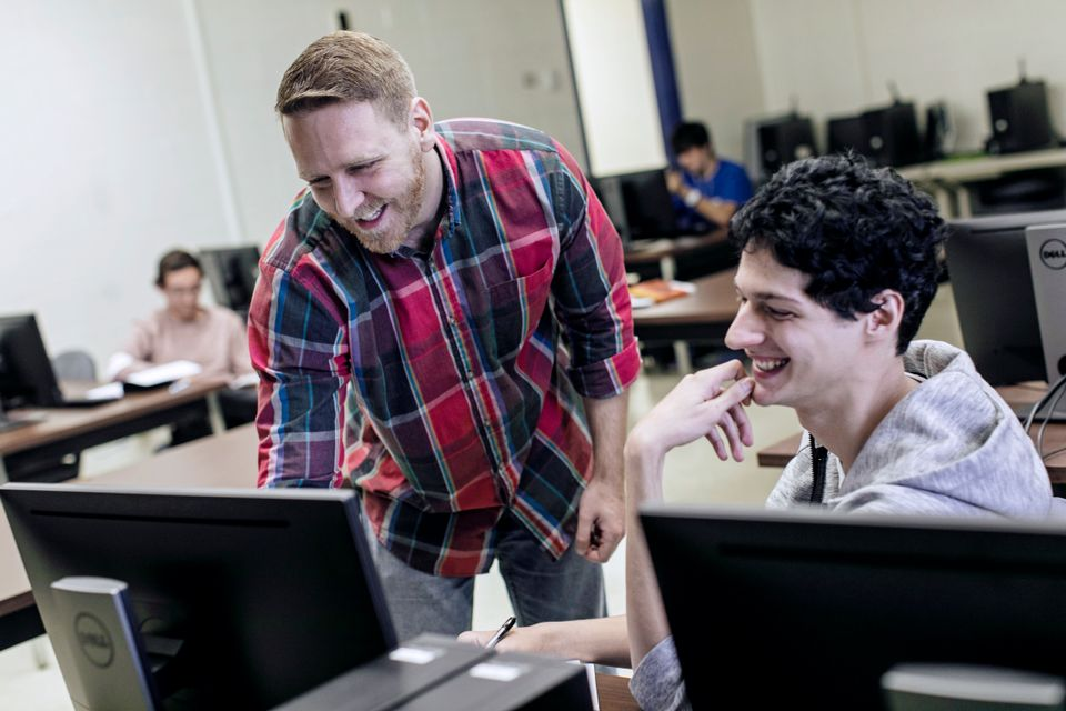 A computer information systems professor teaching a student how to complete a project.