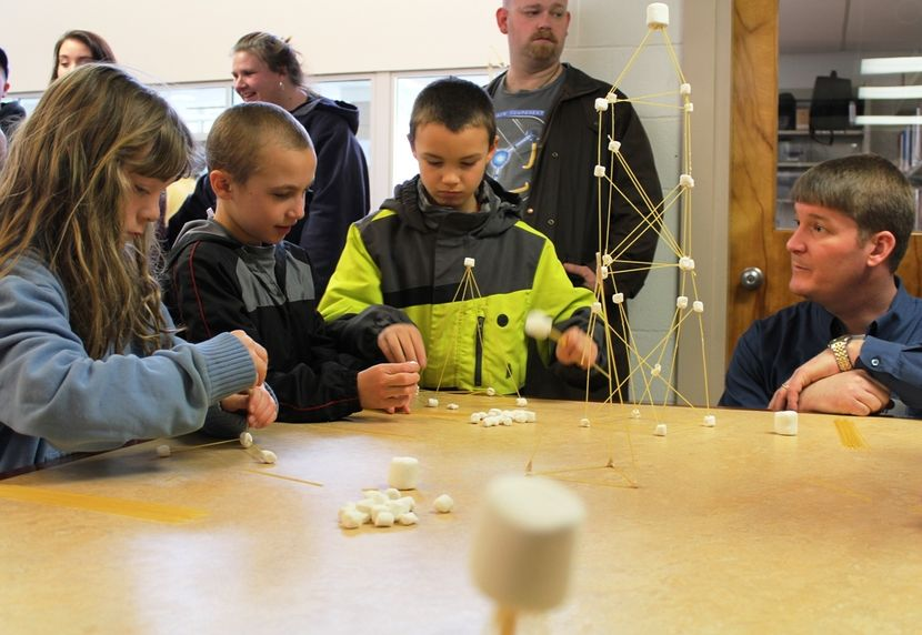 Children attending last year's Mineral County STEM Festival were challenged to build the tallest tower out of spaghetti straws that would support the largest marshmallow. Lending some advice is Brandon Felton, far right, a mechanical engineer with RK&K Ci