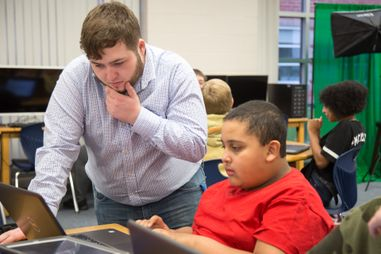 College aged student helping middle school student with coding on laptop