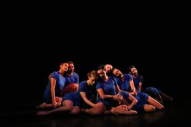 Group of dancers in blue costumes grouped in pose on the floor