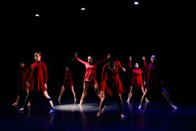 Active group of dancers in red flowing dresses mid-movement on a dark stage