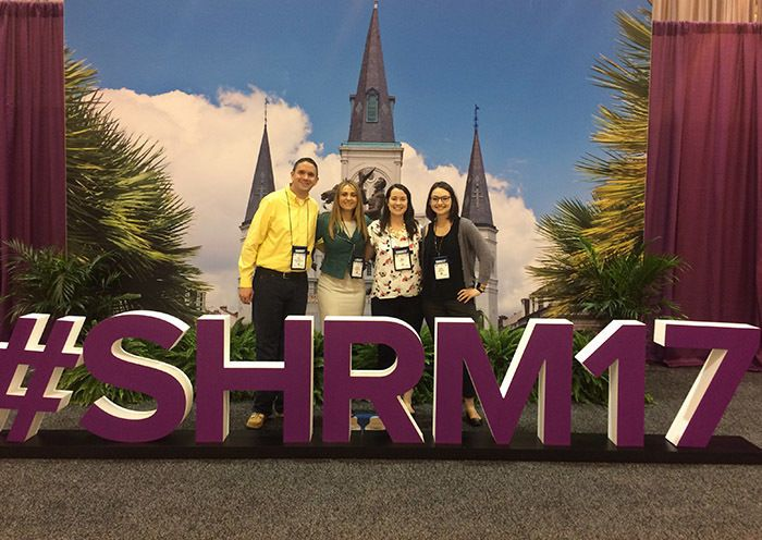"group of people standing behind a sign that says ""SHRM17"""