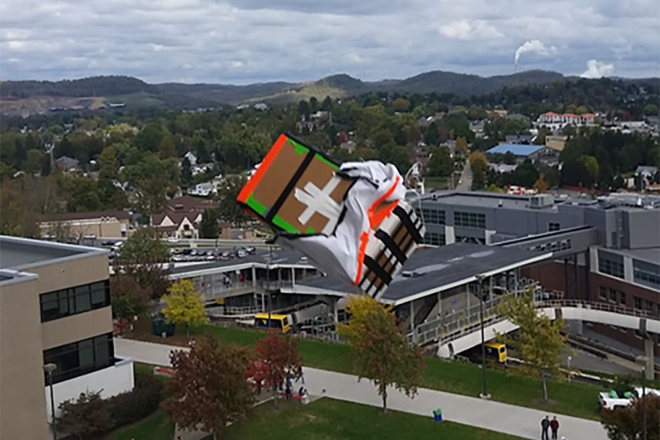 A pumpkin plunges from the roof of the Engineering Sciences building in a cardboard box.