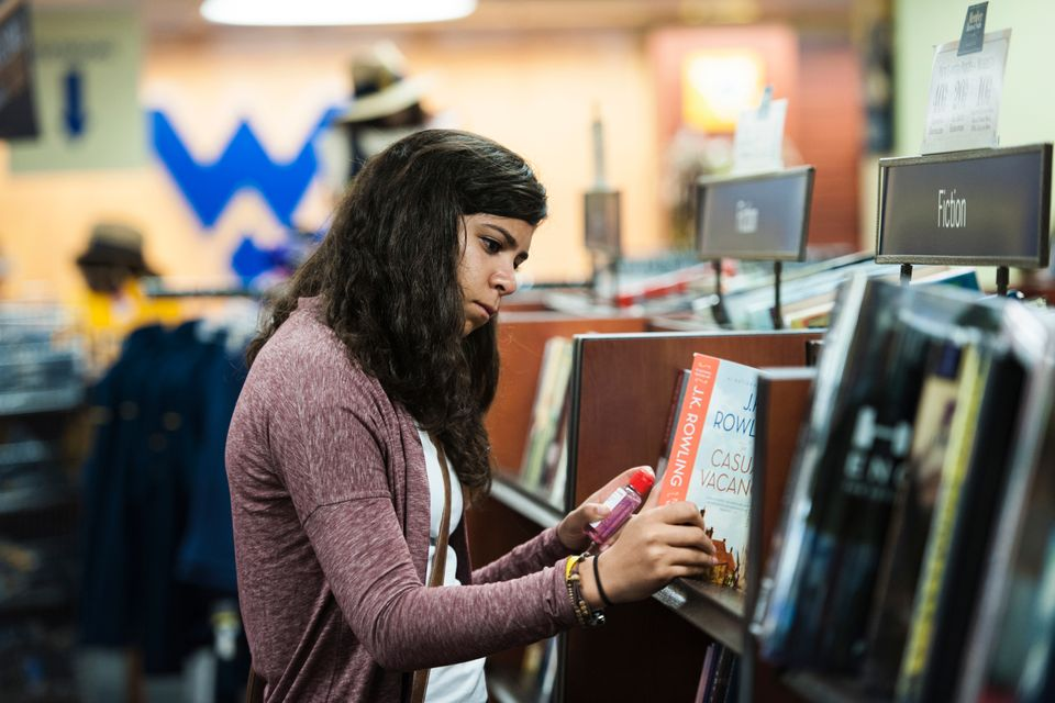 Girl looking at books on a shelf