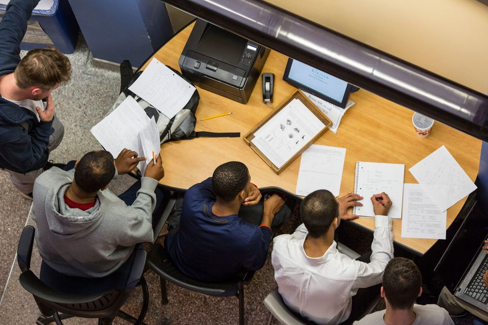 Four Students studying around a desk with papers on it
