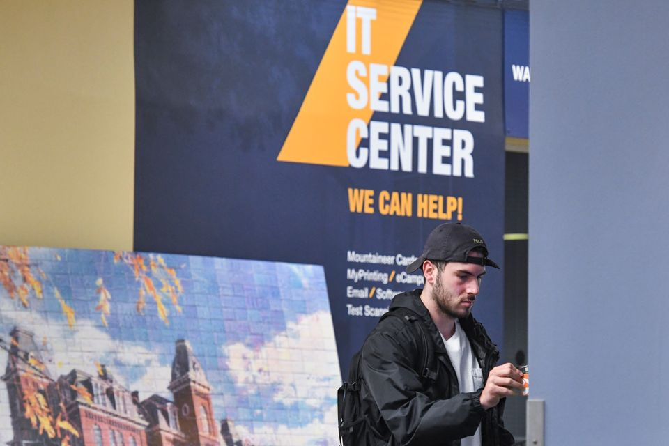 Student standing in front of IT service center sign