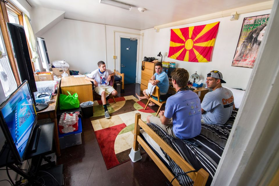 Four students conversing in a dorm room