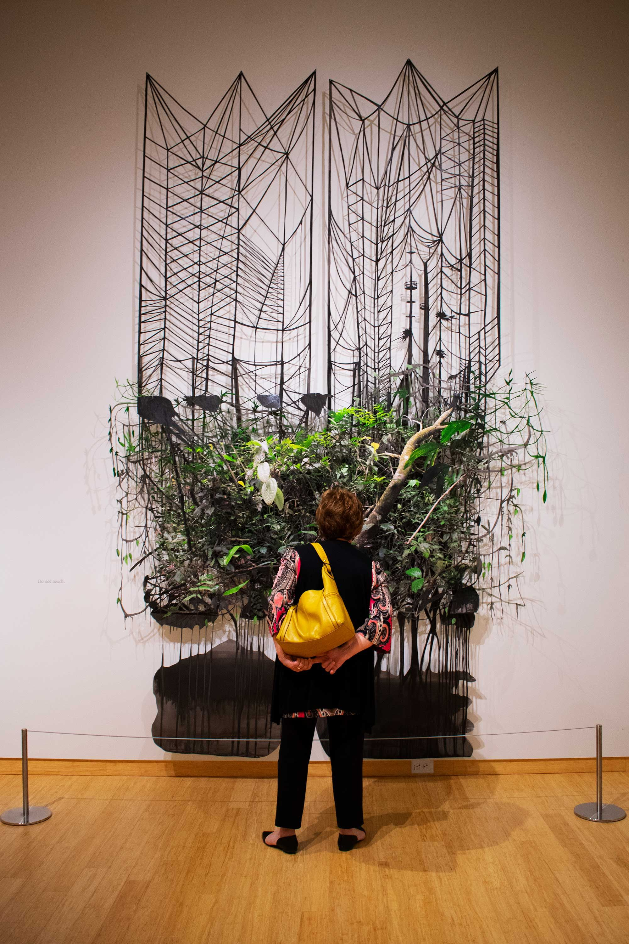 woman stands in front of art wth plants