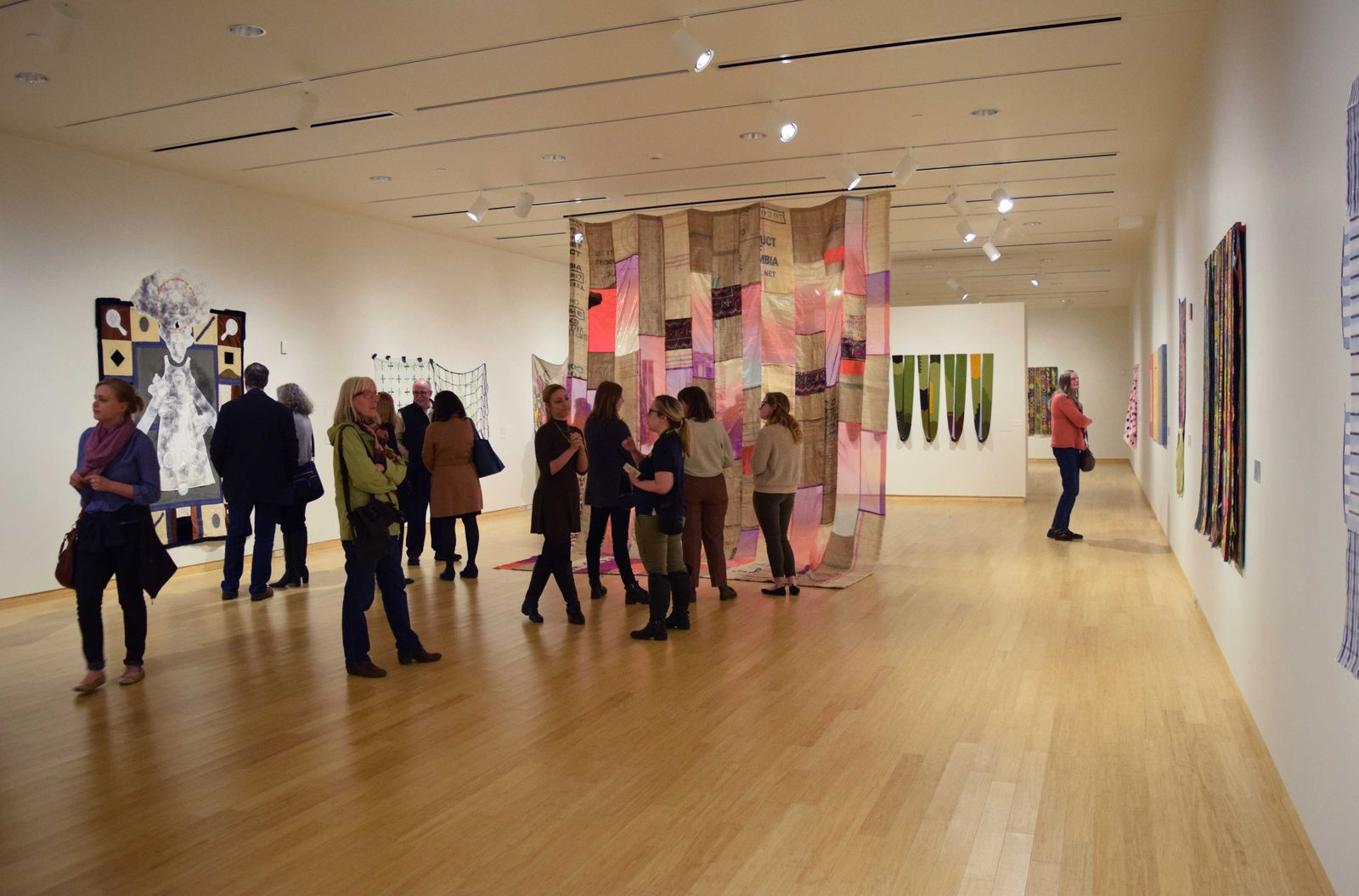 students looking at fabric hanging in gallery