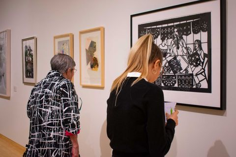 two visitors look at art on the gallery wall