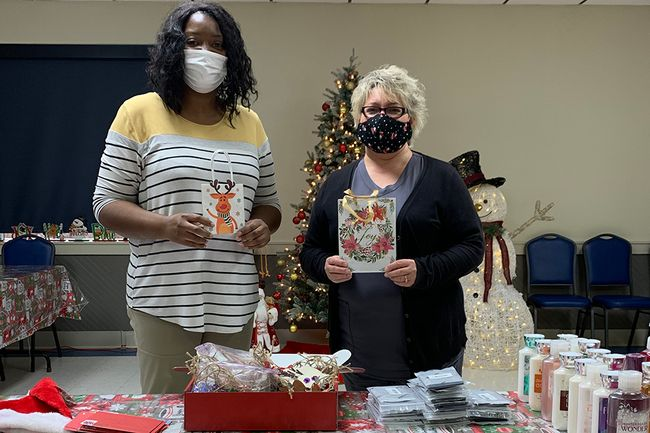Two women put together holiday gift bags