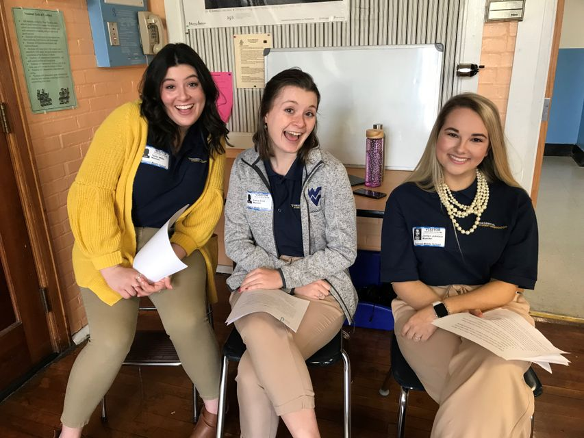 Hannah Belt, Emma Blair, and Jordyn Johnson prepare to discuss different majors with middle school students in Morgantown.