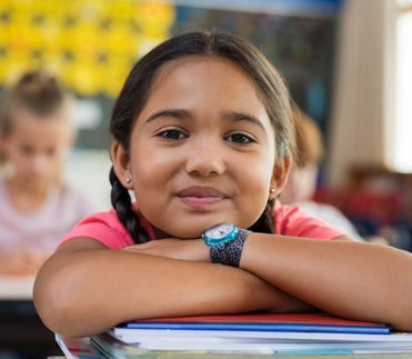 Young girl in a classroom looks confidently into the camera while leaning on her desk.