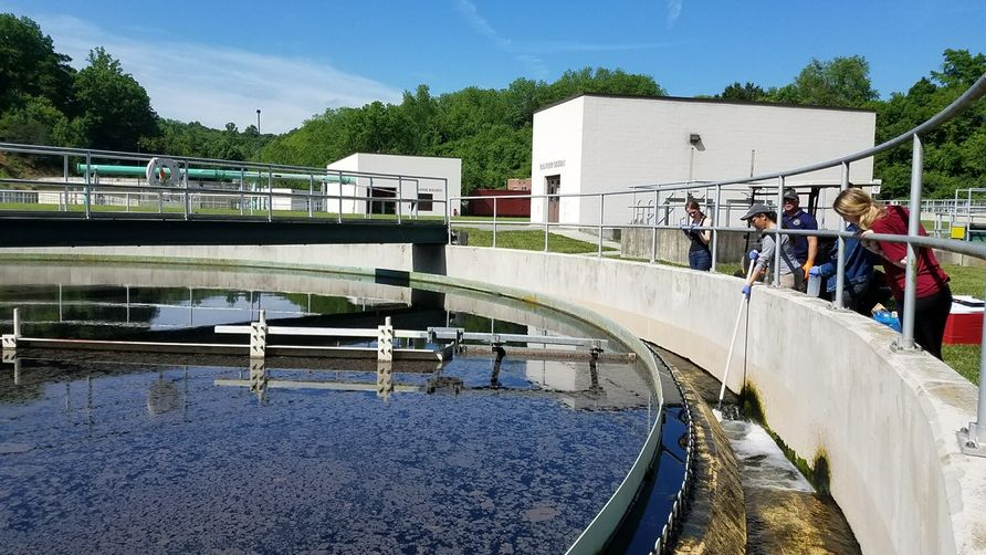 Students collect water from a large tank at a wastewater treatment plant.