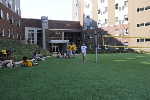 students with volleyball net in yard