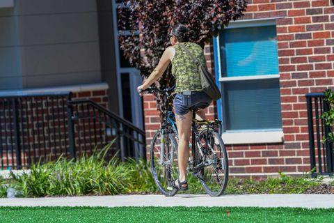 girl riding bike outside apartments
