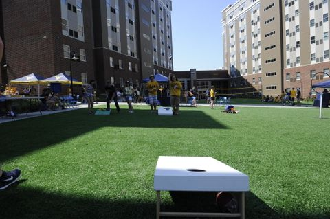 students playing cornhole on the lawn