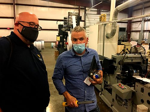 Two men in masks having a discussion in an industrial environment