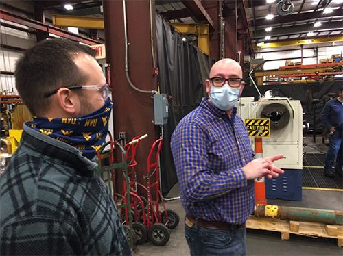 Two men are having a discussion in an industrial environment.