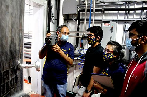 Instructor demonstrates the use of some technical equipment to a small group of students in an industrial environment