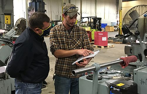 Machine worker reviews document with a man in an industrial environment