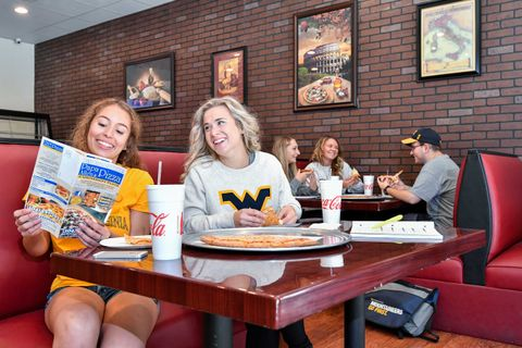 students laughing at a pizza shop