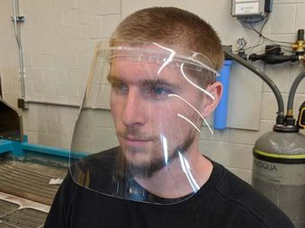 Logan Forquer, student worker, wears the face shield created by the Innovation Hub.