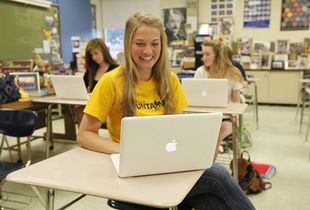 High school student sitting at her desk laughing.