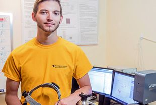 Male student standing in lab.