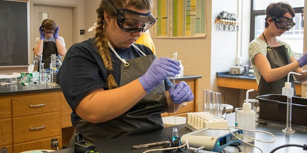 Person wearing goggles and gloves in lab