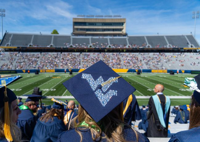 Graduation cap with the Flying WV and Milan Piskar Stadium in the background