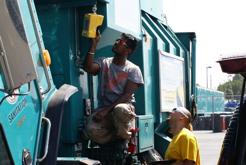 Arvind Thiruvengadam (left) and Saroj Pradhan (right) check for leaks in the natural gas fuel system of a refuse truck.