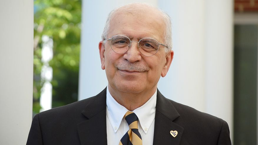 An image of Sam Ameri in a black suit wearing a gold and blue stripped tie, a white dress shirt, and a wvu heart pin on his breast.