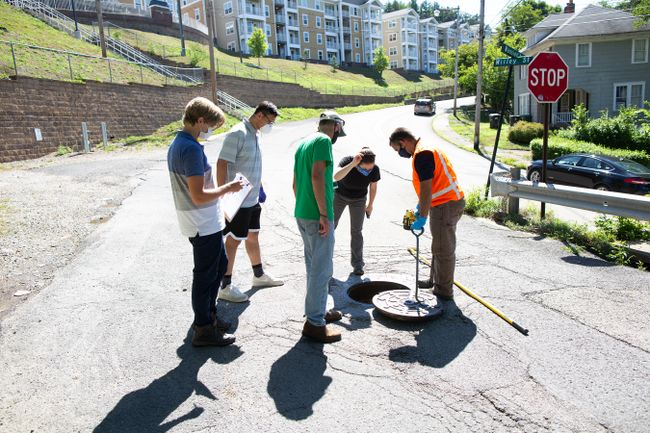 Members of the WVU COVID-19 wastewater testing team prop open a manhole cover near student housing to collect a wastewater sample.