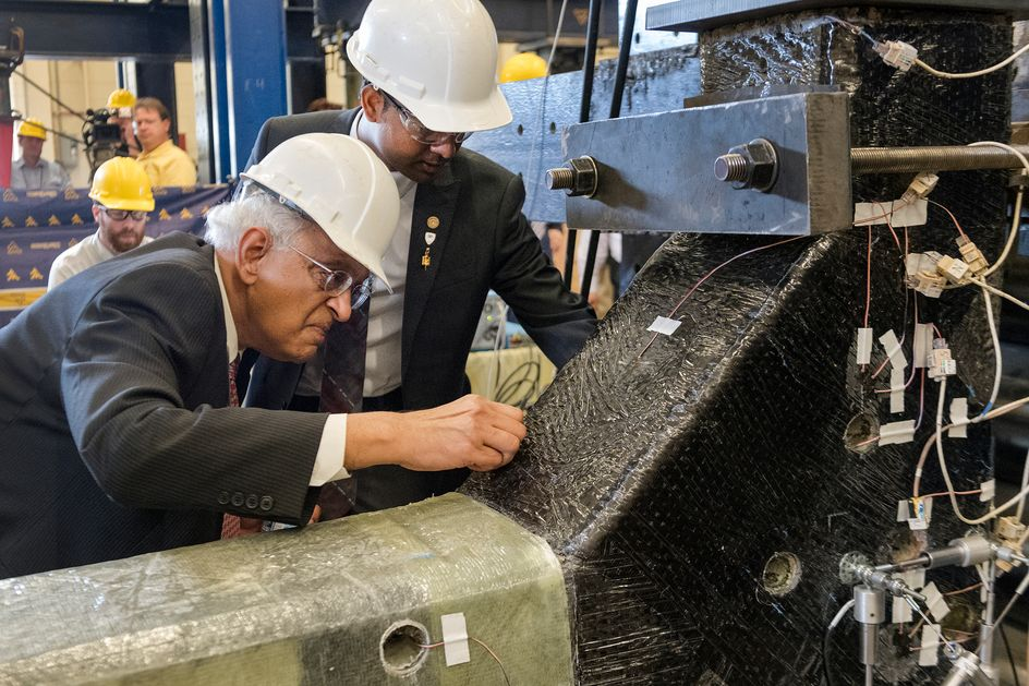 Photo of Hota GangaRao and Praveen Majjigapu inspecting the material structure.