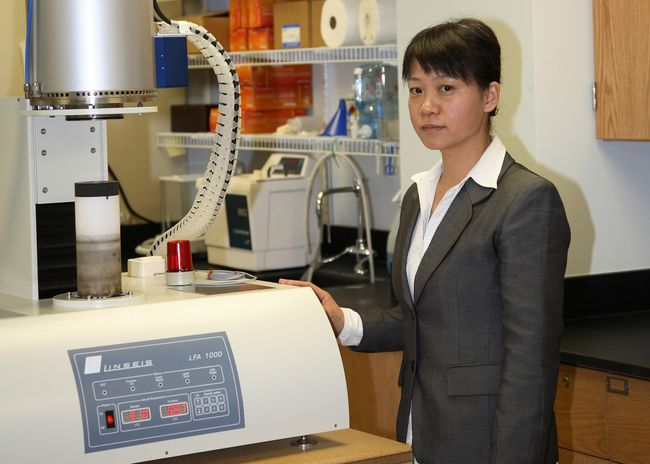 A portrait of Xueyan Song behind a piece of lab equipment.