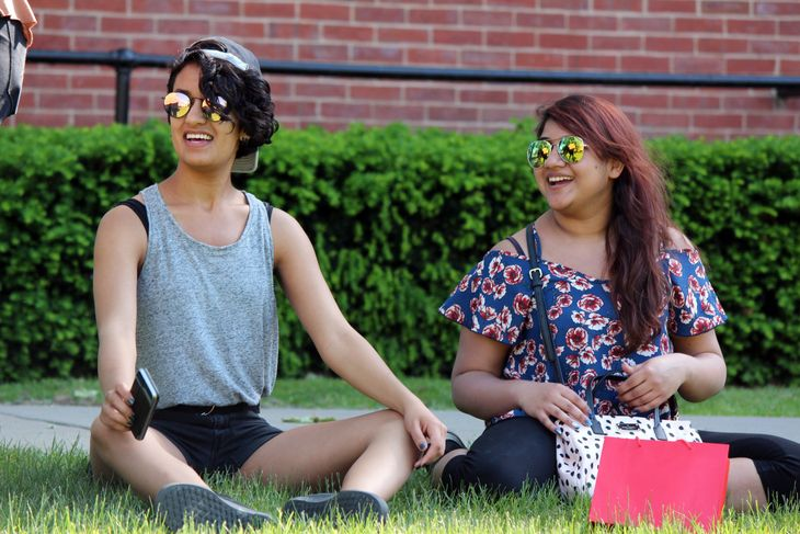 Sofia Lateef laughs with friends while sitting on campus in Woodburn Circle.