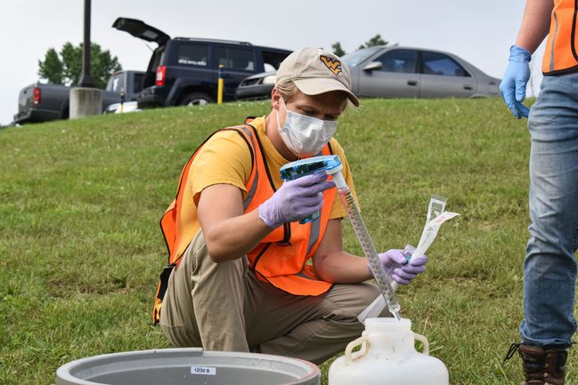 Eric takes a sample of wastewater out of a bucket.